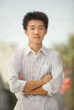Portrait of Smiling Young Man with arms crossed in Nanluoguxiang, Beijing, China Stock Photo