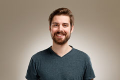 Portrait of smiling young man with beard. On neutral background Stock Photos