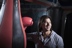 Portrait of smiling young man at the boxing gym leaning on punching bag Stock Photography