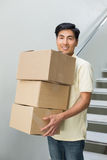 Portrait of a smiling young man carrying boxes Stock Photo