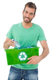 Portrait of a smiling young man carrying recycle container Royalty Free Stock Photo