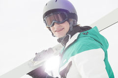 Portrait of smiling young man carrying skis against clear sky Royalty Free Stock Images