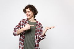 Portrait of smiling young man in casual clothes standing, pointing index finger, hand aside isolated on white wall stock photography