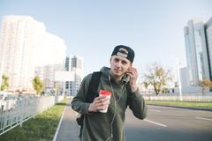 Portrait of a smiling young man with a cup of coffee in his hands, listening to music in headphones against the background of the. City and looking at the Royalty Free Stock Photography