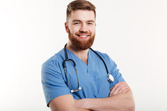 Portrait of a smiling young man doctor with stethoscope standing with arms folded Royalty Free Stock Image