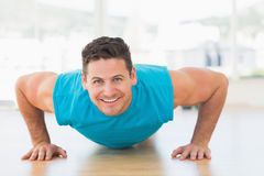 Portrait of a smiling young man doing push ups Stock Image