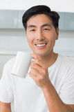 Portrait of a smiling young man drinking coffee in kitchen Royalty Free Stock Image