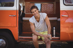 Portrait of smiling young man drinking coffee while sitting in van. At forest Stock Photo