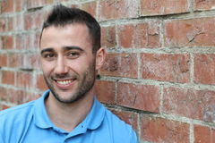 Portrait of Smiling Young Man with Facial Hair Wearing Blue Polo Shirt and Leaning Against Brick Wall Stock Photography