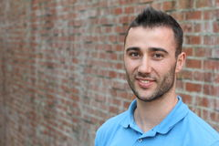 Portrait of Smiling Young Man with Facial Hair Wearing Blue Polo Shirt and Leaning Against Brick Wall Stock Photo