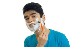 Portrait of a smiling young man with foam on his face who shaves his beard and looks into the camera close-up Royalty Free Stock Photos
