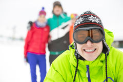Portrait of smiling young man with friends in background during winter Royalty Free Stock Images