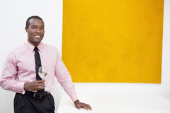 Portrait of smiling young man in front of painting Stock Image
