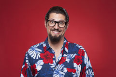Portrait of a smiling young man in Hawaiian shirt against red ba Stock Image