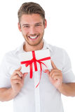 Portrait of smiling young man holding gift Stock Photos