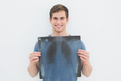 Portrait of a smiling young man holding lung xray Royalty Free Stock Photography