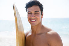 Portrait of smiling young man holding surfboard at beach. On sunny day Royalty Free Stock Photography
