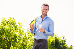 Portrait of smiling young man holding wine bottle and glass Stock Image