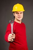 Portrait of a smiling young man holding a wrench Stock Photos