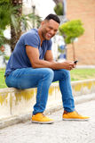 Smiling young man with mobile phone sitting on sidewalk. Portrait of smiling young man with mobile phone sitting on sidewalk Royalty Free Stock Images