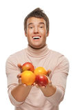Young man with oranges and apples Royalty Free Stock Photos