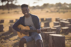 Portrait of smiling young man playing guitar while sitting in forest Royalty Free Stock Photos