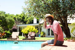 Portrait of smiling young man relaxing by pool Stock Images