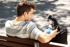 Smiling young man sitting on bench outdoors with bag and using smart phone. Portrait of smiling young man sitting on bench outdoors with bag and using smart Royalty Free Stock Photos