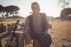 Portrait of smiling young man sitting by guitar on tree stump Stock Photography