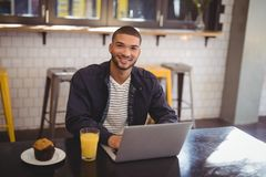 Portrait of smiling young man sitting with laptop at coffee shop stock photos
