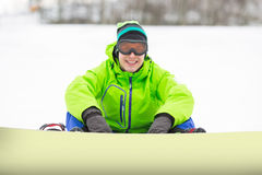Portrait of smiling young man with snowboard sitting on snowy land Stock Photo