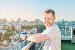 Portrait of smiling young man standing on high rise building balcony with paper cup with hot drink, overlooking inspiring view on Royalty Free Stock Photo