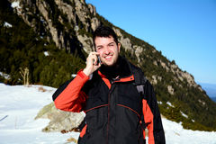 Portrait of smiling  young man talking on the phone in the winter mountain Royalty Free Stock Image