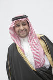 Portrait of smiling young man in traditional Arab clothing and Kaffiyeh, studio shot stock photo