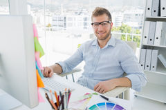 Portrait of a smiling young man using computer Stock Photos