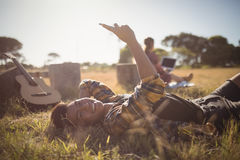 Portrait of smiling young man using mobile phone while lying on field Stock Images