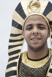 Portrait of smiling young man wearing a headdress from ancient Egypt, studio shot Stock Photography