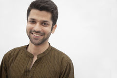 Portrait of smiling young man wearing traditional clothing from Pakistan, studio shot Stock Photo
