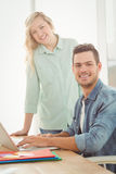 Portrait of smiling young man and woman working on laptop Stock Photo