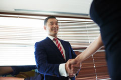 Portrait of a smiling young managing director shaking hands with his business partners while standing in office space interior Royalty Free Stock Photography