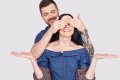 Portrait of a smiling young man covering his girlfriends eyes as a surprise isolated over white background royalty free stock photography