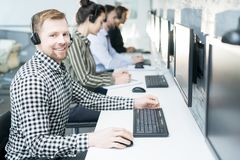 Help Desk Operators. Portrait of smiling young men wearing headset looking at camera while working with group of help desk operators sitting in row, copy space stock photo
