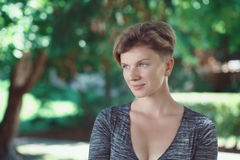 Portrait of smiling young middle aged white caucasian girl woman with short hair stylish haircut  in tshirt looking away Royalty Free Stock Photo
