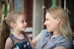 Portrait of a smiling young mother and daughter close-up outdoors. The concept of family relations Royalty Free Stock Photo