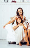 Portrait of smiling young mother and daughter at home, happy fam Stock Images
