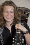 Portrait of smiling young musician with guitar over shoulder Royalty Free Stock Photos