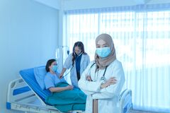 Portrait of smiling young muslim female doctor arms crossed stand in hospital with medical team working on the background
