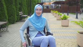 Portrait smiling young muslim woman disabled in traditional scarf sitting in a wheelchair in the park. Portrait smiling young attractive muslim woman disabled in stock footage