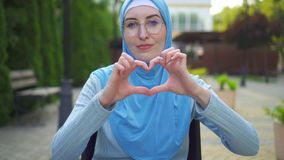Portrait smiling young muslim woman disabled in traditional scarf sitting in a wheelchair in the park and shows hands. Portrait smiling young attractive muslim stock video