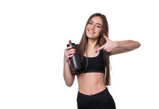 Portrait of smiling young sporty woman with a bottle of water posing in studio isolated on white background. Royalty Free Stock Images